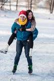 Couples heureux ayant le patinage de glace d'amusement sur la piste dehors Photos stock