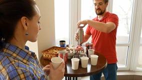 Couples heureux ayant un thé potable de coupure de casse-croûte Image libre de droits