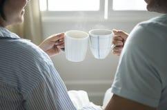 Couples heureux célébrant avec des tasses de café Images stock