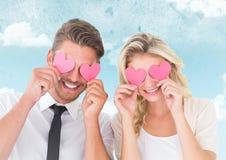 Couples heureux cachant leurs yeux avec le coeur Photo libre de droits