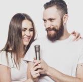 Couples heureux chantant dans le karaoke au-dessus du fond blanc, Images stock