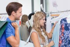 Couples heureux choisissant de nouveaux vêtements Image libre de droits