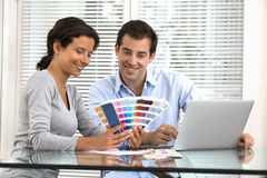 Couples heureux choisissant des couleurs pour peindre la nouvelle maison Photographie stock libre de droits