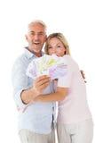 Couples heureux clignotant leur argent liquide Photos stock