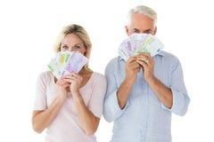 Couples heureux clignotant leur argent liquide Images stock