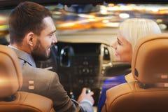 Couples heureux conduisant dans la voiture au-dessus de la ville de nuit Photo stock