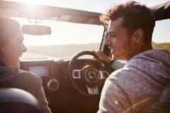 Couples heureux conduisant dans la voiture avec le toit ouvrant ouvert, passager POV photos libres de droits