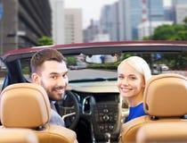 Couples heureux conduisant dans la voiture de cabriolet au-dessus de la ville Photographie stock libre de droits