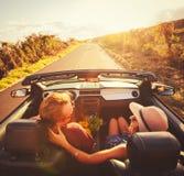 Couples heureux conduisant dans le convertible Photographie stock