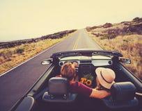 Couples heureux conduisant dans le convertible Photo stock