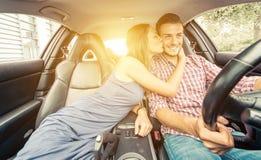 Couples heureux conduisant sur une voiture de sport Photos libres de droits