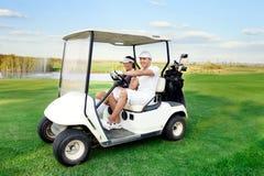 Couples heureux conduisant un golf-chariot Images libres de droits
