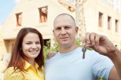 Couples heureux contre construire la nouvelle maison Image stock