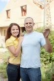 Couples heureux contre la nouvelle maison de construction Photo stock