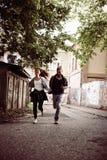Couples heureux courant ensemble la rue de cuvette Photos libres de droits