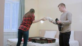 Couples heureux déballant la valise venant juste à une chambre d'hôtel Photos stock