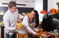 Couples heureux décidant des fruits dans la boutique photographie stock libre de droits