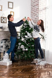 Couples heureux décorant l'arbre de Noël Homme et femme de sourire à Photos libres de droits