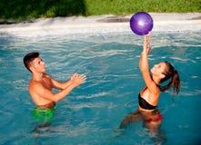 Couples heureux détendant dans la piscine jouant avec une boule Photos stock