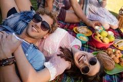Couples heureux détendant en parc tout en ayant le pique-nique Image stock