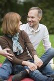 Couples heureux détendant en stationnement Photographie stock