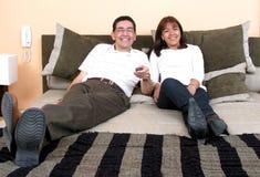 Couples heureux détendant et regardant la TV Images stock