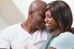 Couples heureux détendant sur le divan Images libres de droits