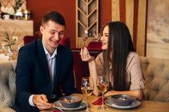 Couples heureux dînant au restaurant et à rire Image stock