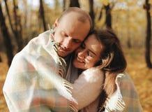 Couples heureux d'épouse et de son abri de mari dans le plaid en automne Fermez-vous vers le haut de tenir des mains La famille g photo libre de droits