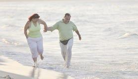 Couples heureux d'aînés sur la plage Photographie stock libre de droits