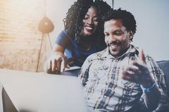 Couples heureux d'afro-américain détendant ensemble sur le sofa Jeunes homme de couleur et fille à l'aide de l'ordinateur portabl Photos stock