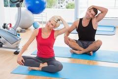 Couples heureux d'ajustement travaillant au tapis d'exercice Photos stock