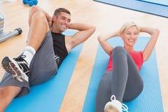 Couples heureux d'ajustement travaillant au tapis d'exercice Photographie stock libre de droits