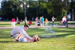 Couples heureux d'amour ayant l'amusement avec un chariot à supermarché dans le parc Photographie stock