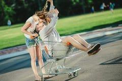 Couples heureux d'amour ayant l'amusement avec un chariot à supermarché dans le parc Photographie stock libre de droits