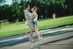 Couples heureux d'amour ayant l'amusement avec un chariot à supermarché dans le parc Image stock