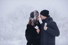 Couples heureux d'amour dans la forêt au coeur de papier d'hiver, de promenade, de baiser, d'étreinte et de prise en parc - jour  Photo libre de droits