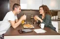 Couples heureux d'amour parlant à la maison de petit déjeuner Photos libres de droits