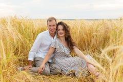 Couples heureux d'amour se reposant dans le blé sur le champ Photo libre de droits
