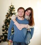 Couples heureux d'hiver dans l'amour à la maison sur l'arbre de Noël de fond Image libre de droits