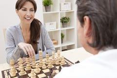 Couples heureux d'homme et de femme jouant aux échecs Photo stock