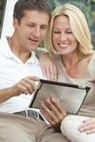 Couples heureux d'homme et de femme utilisant l'ordinateur de tablette Image libre de droits