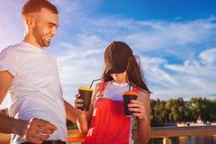 Couples heureux d'université dans l'amour ayant l'amusement tout en buvant du café dehors Types riant sur le pont au coucher du s Photo libre de droits