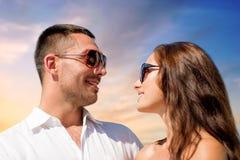 Couples heureux dans des lunettes de soleil au-dessus de fond de ciel photos stock