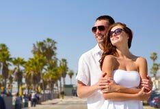 Couples heureux dans des lunettes de soleil au-dessus de plage de Venise Photo stock
