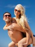 Couples heureux dans des lunettes de soleil sur la plage Images libres de droits