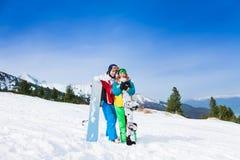 Couples heureux dans des masques de ski se tenant ensemble Photographie stock
