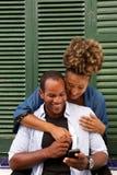 Couples heureux dans l'étreinte avec l'homme tenant le téléphone portable Images stock