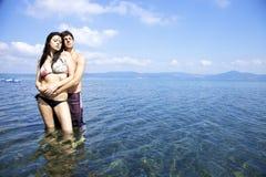 Couples heureux dans l'amour étreignant dans l'eau Photo libre de droits