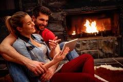 Couples heureux dans l'amour étreignant et à l'aide du comprimé ensemble Image stock